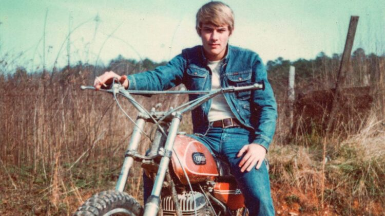 A vintage photo of a young man sitting astride a motorcycle