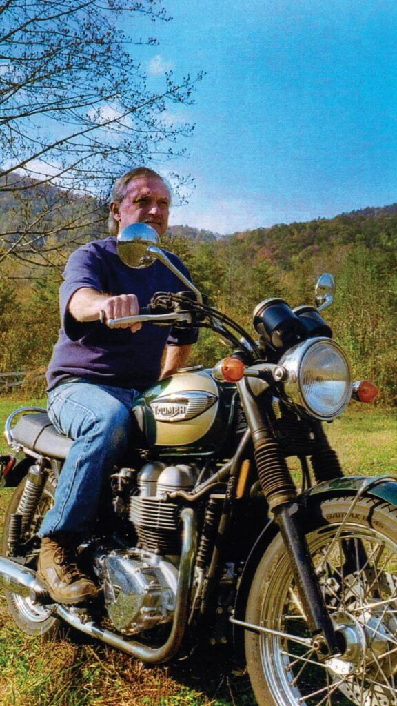 A modern photo of an older man sitting astride a motorcycle