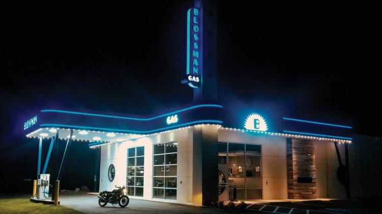 A motorcycle in front of an illuminated gas station at night