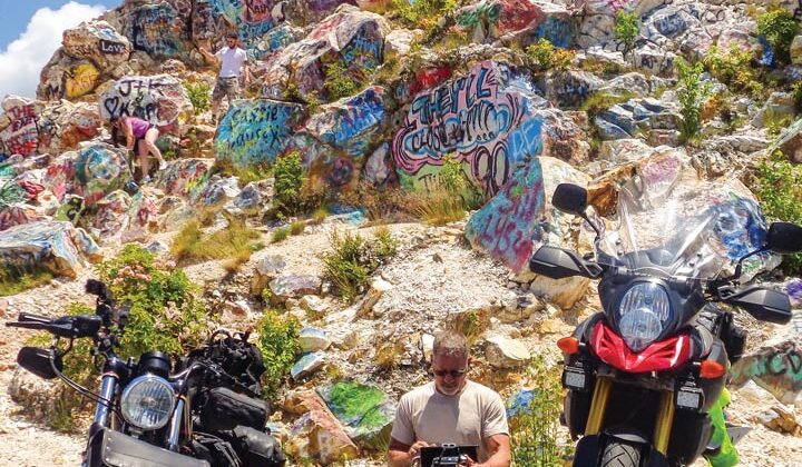 A man seated in front of brightly painted boulders prepares a drone for flight
