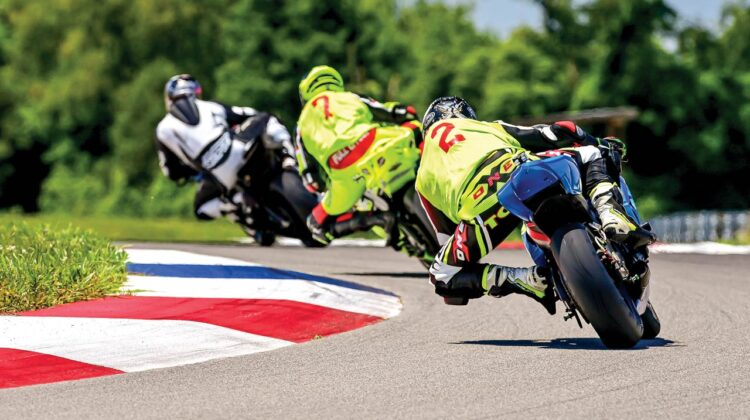 Motorcycle riders round a tight curve on a racetrack