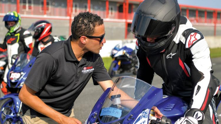 An instructor talks with a student on a motorcycle