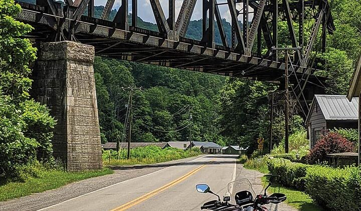 A motorcycle is in the foreground with a railroad trestle in the background