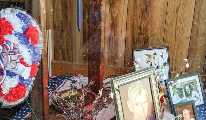 Framed portraits and americana are seen in a storefront