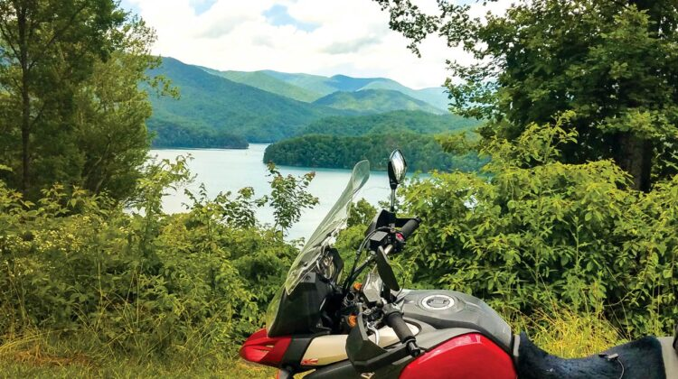 A motorcycle is in the foreground with a lake in the background