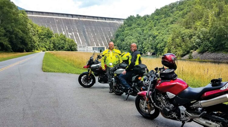 Two men with three motorcycles are parked in front of a dam