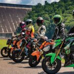 A group of motorcycle riders is parked in front of a dam