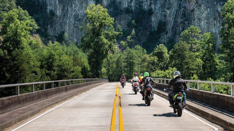 A group of motorcycle riders crosses a bridge with a rock cliff in the background