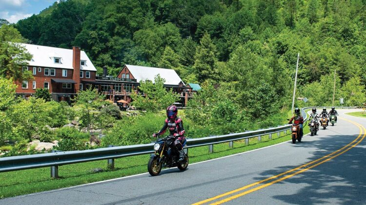 A group of motorcycle riders makes its way past an old lodge