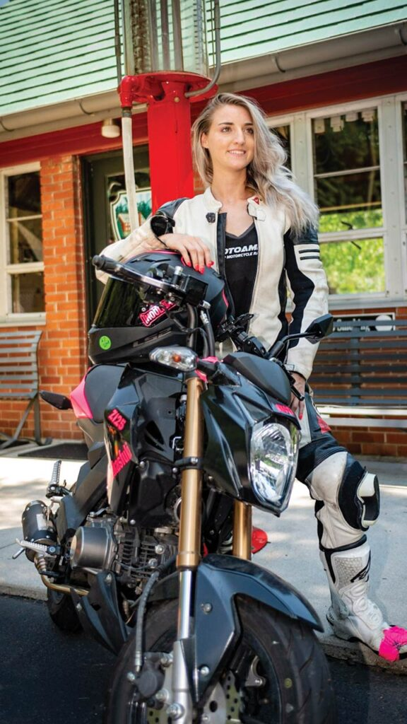 A young woman sits astride a black motorcycle