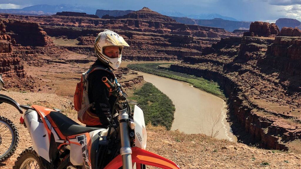 A man sits astride a motorcycle overlooking a desert landscape