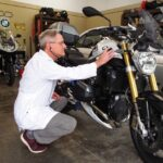 A man in a lab coat uses a stethoscope on a BMW motorcycle
