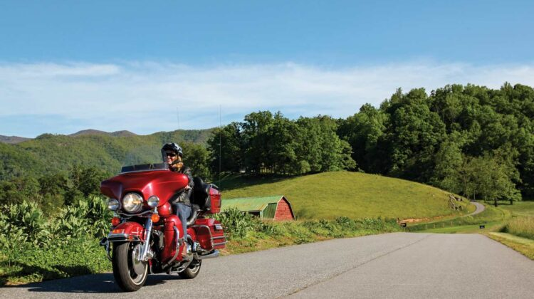 A woman rides a red Harley-Davidson through a rural setting
