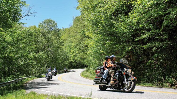 Four motorcycles wind their way down a rural mountain road
