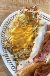 A plate of hashbrowns and bacon at Waffle House.