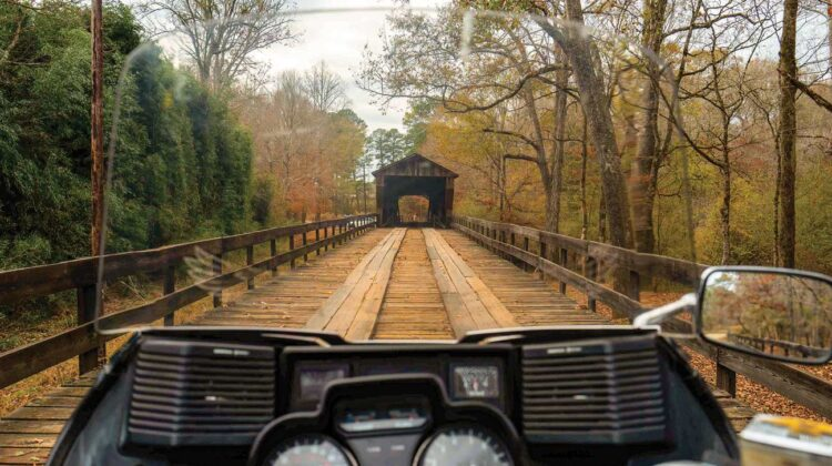 View over the dashboard of a motorcycle looking ahead to the opening of a covered bridge.
