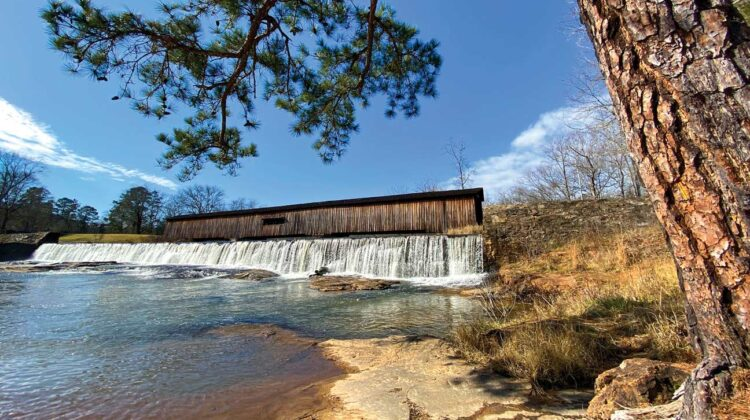 View of a waterfall with a covered bridge spanning the background.