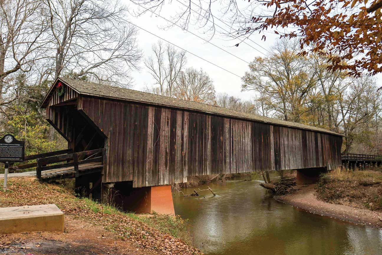 Side view of a covered bridge over a peaceful stream.