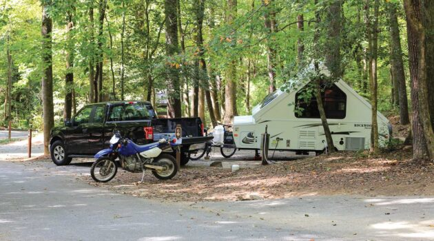 A pickup with an RV is parked in a campsite alongside a motorcycle