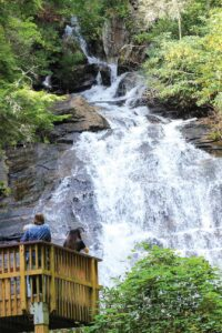 A couple stands at the base of a waterfall