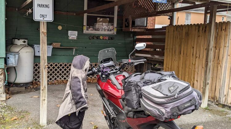 """A red motorcycle with luggage is parked beside a """"motorcycle parking only"""" sign"""