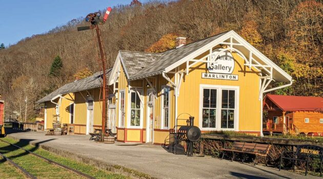 A historic train depot sits beside a disused railroad track