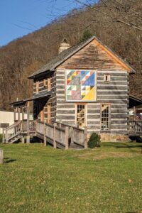 A historic log house with a large quilt square on the side