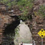 A rider goes through the rocky opening of a stone formation
