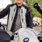 A gear-clad rider stands behind his BMW motorcycle.