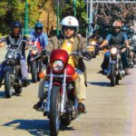 Well-dressed men ride motorcycles across a bridge