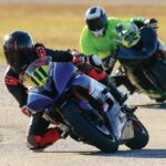 Two motorcycle riders lean into a curve during a track event.
