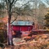 a distant view of a covered bridge in autumn